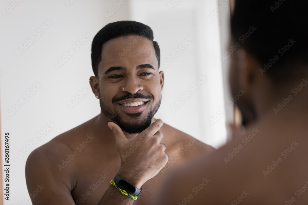Fototapeta Smiling young african American man look in mirror in bathroom touch shaved bristle or beard, happy biracial millennial male take care do daily beauty facial procedures in bath, skincare cocnept