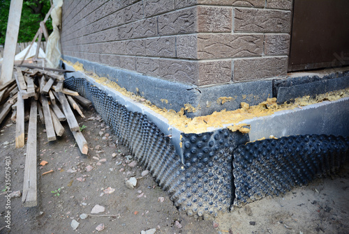 Valokuva Installing dimpled membrane, drainage sheet, vapor barrier for waterproofing and drainage, sealed with foam on the exterior poured concrete wall foundation, basement