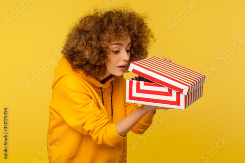 Valokuva Portrait of funny curious nosy curly-haired woman in urban style hoodie looking into gift box, unwrapping present and peeking inside with interest
