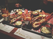 High Angle View Of Stuffed Lobster With Fries And Salad On Tray