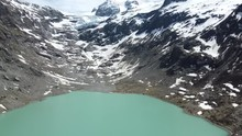 Drone Flight Over A Deep Green Lake To The Trift Glacier In The Swiss Alps