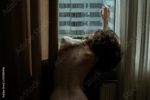 Woman naked back relax by window, hand on glass. Stay isolation at home. Sensual beautiful girl skin. Sexy nude body background. Apartment Building. Social Distancing. Portrait sexy female slim figure