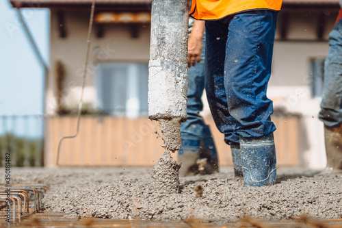 Fototapety, obrazy: worker pouring concrete with automatic pump. Details of construction site and close up details of worker workwear