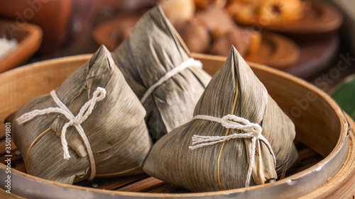 Fototapeta Rice dumpling, zongzi - Chinese rice dumpling zongzi in a steamer on wooden table with red brick, window background at home for Dragon Boat Festival concept, close up. obraz