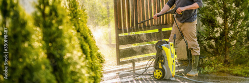 Unrecognizable man cleaning a wooden gate with a power washer Fototapet