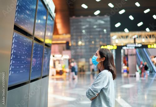 Obraz Woman in virus protection face mask looking at information board checking her flight in international airport - fototapety do salonu