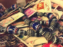 High Angle View Of Postage Stamps And Beads Necklace On Table