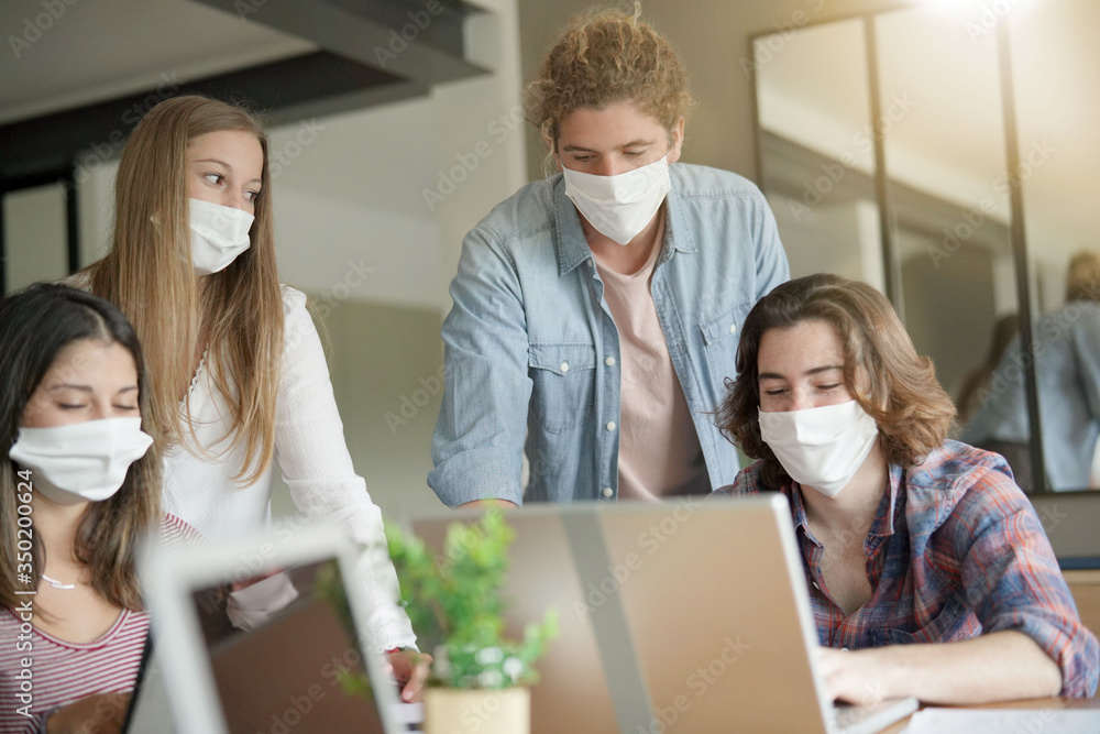 Fototapeta group of students working wearing masks