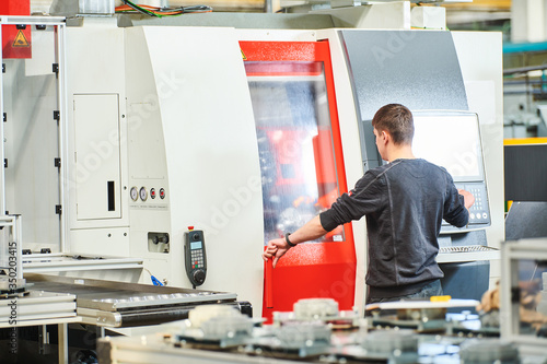 Canvastavla Industrial worker operating cnc machine at metal machining industry