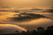 Mountains in fog at beautiful morning in autumn in Dalat city, Vietnam. Landscape with Langbiang mountain valley, low clouds, forest, colorful sky , city illumination at dusk.