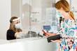 canvas print picture - dentro un locale commerciale la cliente paga alla cassa con carta di credito munita di mascherina e separata dalla cassiera da un separatore di plexiglass