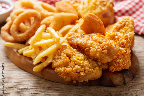 Fotomural fast food meals : onion rings, french fries, chicken nuggets and fried chicken