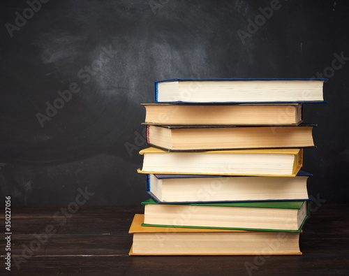 stack of various hardback books on the background of an empty black chalk board Slika na platnu