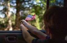 Young Boy Flying American Flag In Freedom And Pride.