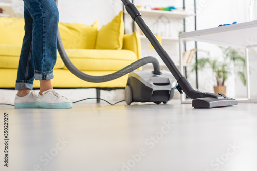 Fototapeta Cropped view of woman with vacuum cleaner near coffee table in living room obraz