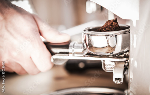Fototapeta Male Grinding Coffee In Barista Machine. obraz