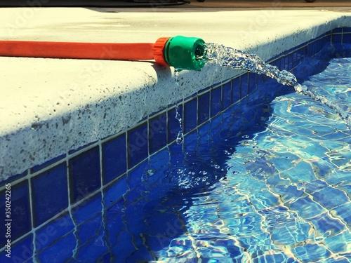 Fotografie, Obraz Hose Spraying Water In Swimming Pool