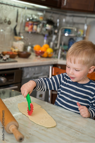 Fotografering Little cute blond boy in kitchen is learning to cut flour dough with children's shaped baking knife