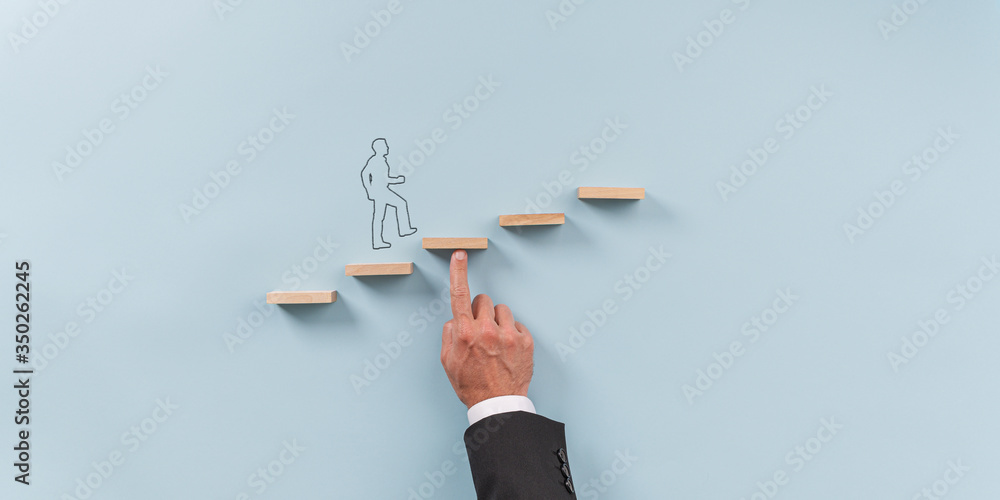 Fototapeta Hand of a businessman supporting wooden step for a silhouetted man to walk upwards