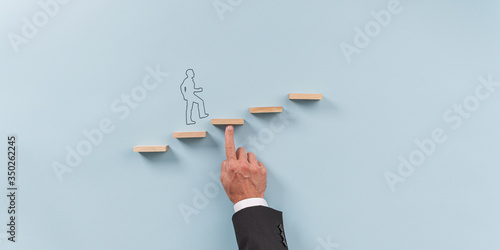 Hand of a businessman supporting wooden step for a silhouetted man to walk upwar Fototapeta