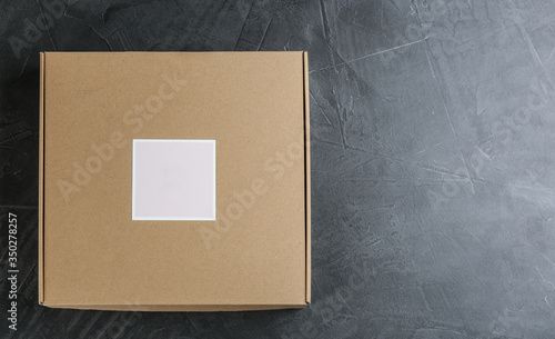 Cuadros en Lienzo Closed cardboard box on grey stone table, top view