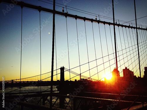 Billede på lærred Silhouette Manhattan Bridge Seen From Brooklyn Bridge Over East River At Sunset