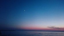 Scenic View Of Crescent Moon In Blue Sky Over Sea During Twilight