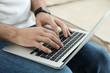 Man working on modern laptop at home, closeup