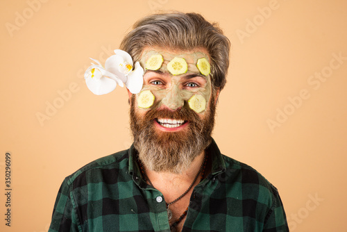 Fotografia, Obraz Funny man applied facial masks and cucumbers on face