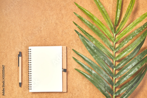 Obraz Pen, prepared to writing on mock up notebook in top view with tropical leaves. - fototapety do salonu