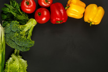 Colorful Bright Vegetables, Tomatoes, Peppers, Broccoli, Avocado, Onions, Spinach And Salad On The Edge Of A Black Background.