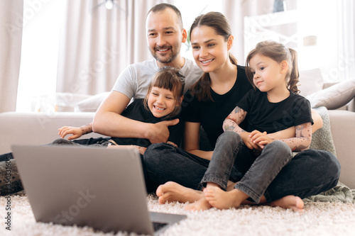 Fototapeta Video call. Happy cheerful family. Young parents and their two amazing daughters communicate via video conference with grandparents sitting at home on the floor  in stylish casual wear obraz