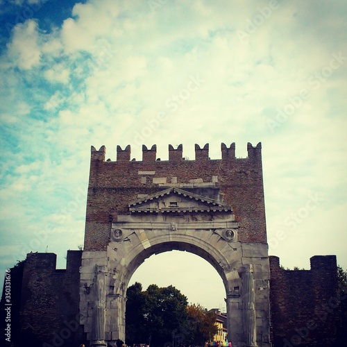Photo Low Angle View Of Arch Of Augustus Against Cloudy Sky