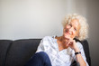 happy older woman relaxing on couch at home