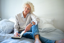 Older Woman Sitting On Bed Wri...