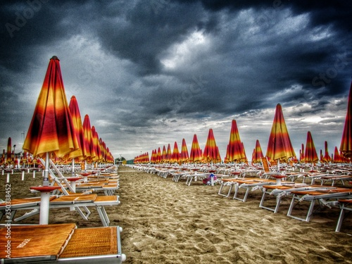Fotografiet Deck Chair And Parasol Against Cloudy Sky