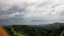 Scenic View Of Green Mountains By Taal Lake Against Cloudy Sky
