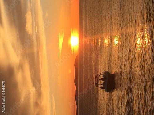 Fototapeta Silhouette People In Motorboat Against Orange Sunset Sky