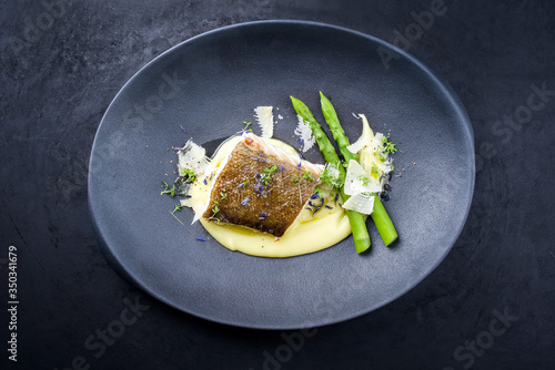 Fototapeta Traditional fried skrei cod fish filet with green asparagus tips and mashed potato creme in parmesan olive oil sauce as top view on a modern design plate with copy space obraz