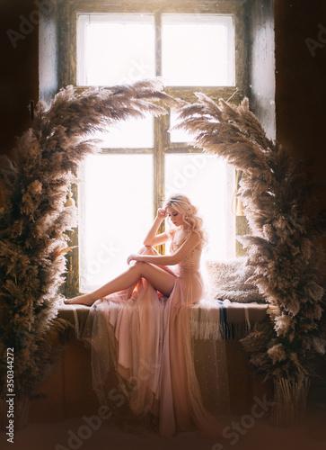 Murais de parede Beautiful sad woman sitting on vintage windowsill retro window