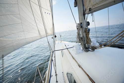 Fototapeta White yacht sailing on a sunny summer day. Close-up view from the deck to the bow and sails. Waves and water splashes. Clear blue sky. Baltic sea, Sweden obraz na płótnie