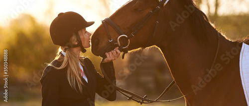 Beautiful horse rider girl stands near a horse on a farm
