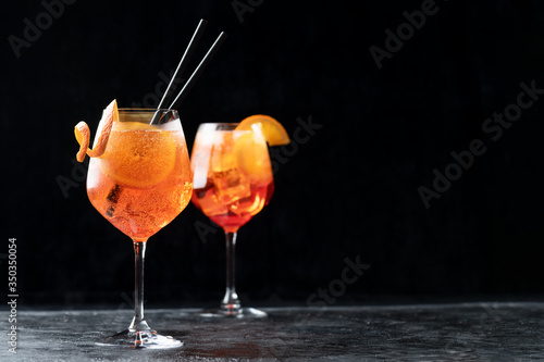 Foto Two glasses of classic italian aperitif aperol spritz cocktail with slice of ora