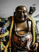 Cropped Hand Touching Laughing Buddha Statue In Temple