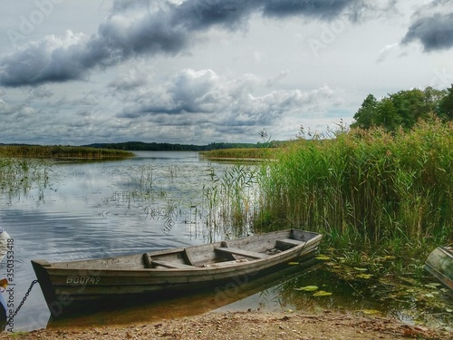 Fototapety, obrazy: Boat At Lakeshore Against Cloudy Sky