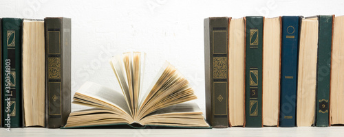 Fotografija Composition with vintage old hardback books, diary, fanned pages on wooden deck table and abstract background