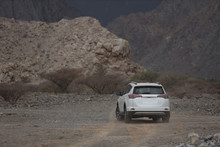 SUV Traveling Through The Deserts And Quarries