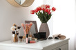 Dressing table with makeup products, accessories and tulips indoors. Interior element