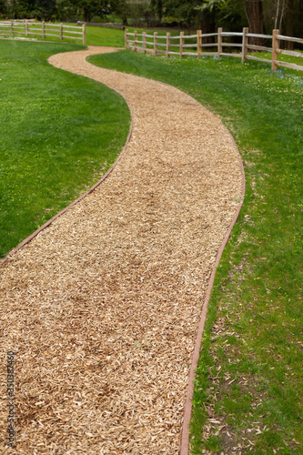 Fotografia, Obraz Foreground focus on a curved wood chip path in a garden