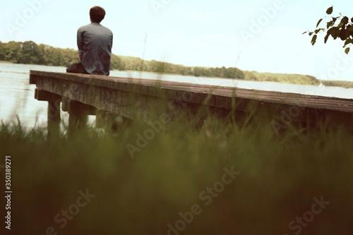 Fototapeta Rear View Of Man Sitting At The Edge Of Pier obraz